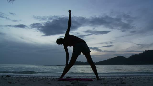 stockvideo's en b-roll-footage met ws silhouette of woman stretching on beach at dusk / seychelles - benen gespreid