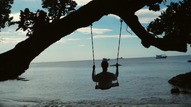 vídeos de stock e filmes b-roll de silhouette of woman swinging on swing on beach at sunset - vietname