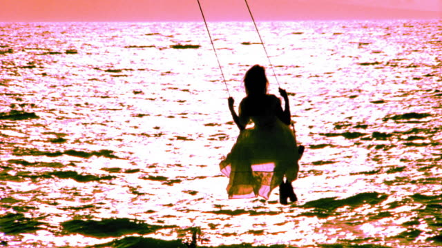 OVEREXPOSED ORANGE REAR VIEW silhouette of woman swinging on tree swing / ocean in background / Hawaii