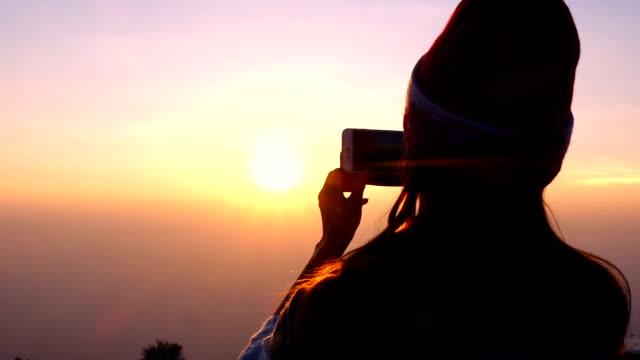 Silueta de mujer tomando fotos de la hermosa vista en Sunrise con Smartphone