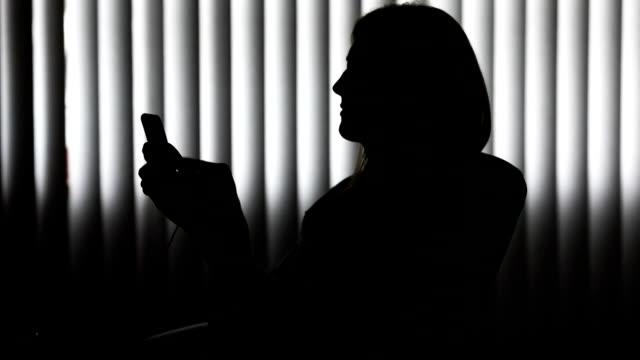 スマート フォン上にテキスト メッセージ女性のシルエット - 横顔点の映像素材/bロール