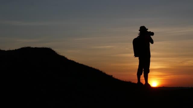 夕日の写真を撮る人の女性カメラマンのシルエット - 撮影点の映像素材/bロール
