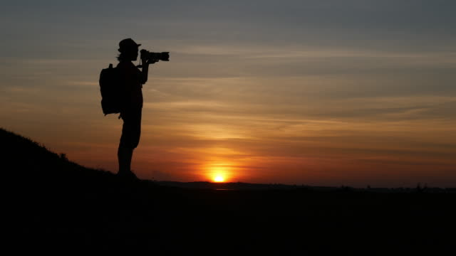 Silhouette of woman-photographer taking photos of sunset