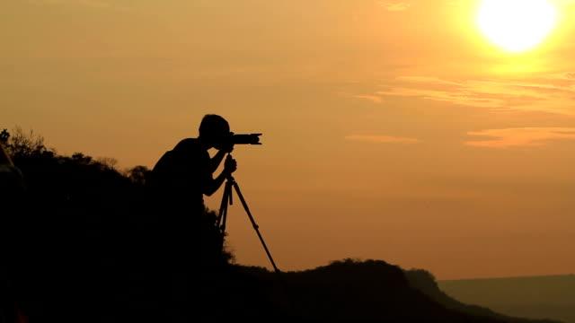 vidéos et rushes de silhouette de femme de prendre une photo avec les montagnes au coucher de soleil. - pince à papier