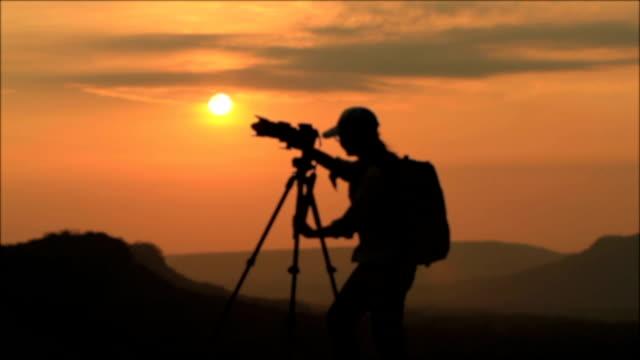 Silhouette der Frau Nehmen Sie ein Foto mit Blick auf die Berge während dem Sonnenuntergang.