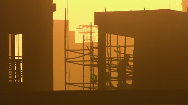 MS Silhouette of worker on construction site at sunrise, Dubai, United Arab Emirates