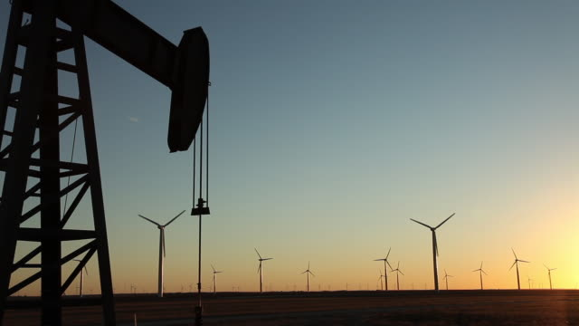 silhouette of working pumpjack by a wind farm at sunset - pump jack stock videos & royalty-free footage
