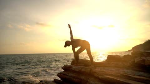 ヨガアジア女性のシルエットがエクササイズをしている - active lifestyle点の映像素材/bロール