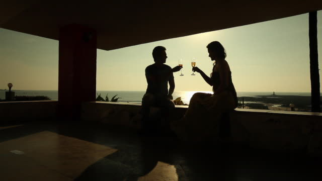 vídeos de stock e filmes b-roll de silhouette of young couple drinking champagne in a resort  - champanhe