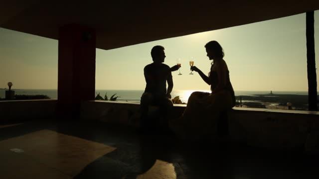 vídeos y material grabado en eventos de stock de silhouette of young couple drinking champagne in a resort  - vino