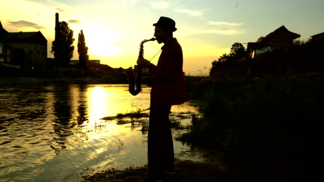 silhouette of young man playing saxophone - blues stock videos & royalty-free footage