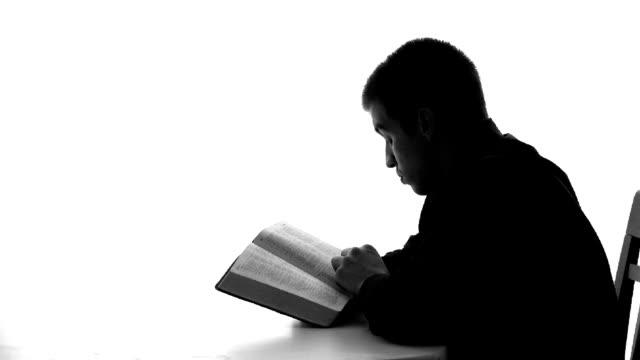 stockvideo's en b-roll-footage met silhouette of young man praying - apostel
