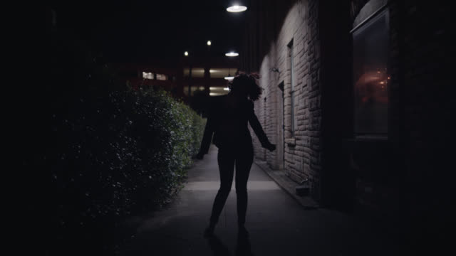 WS SLO MO. Silhouette of young woman dancing in urban alleyway at night.