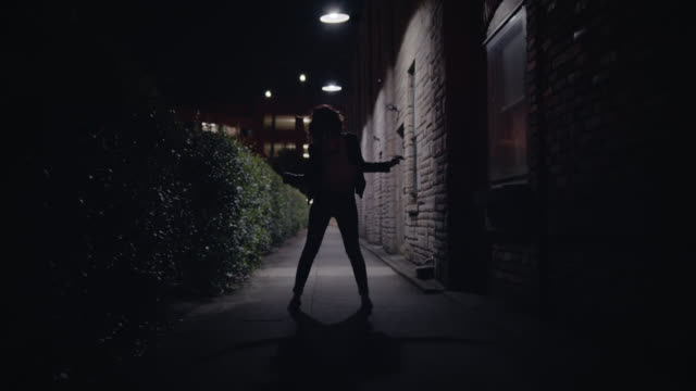 WS SLO MO. Silhouette of young woman dancing under streetlights in city alley.