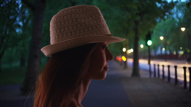 silhouette of young woman in fedora hat outdoors in evening - hat stock videos & royalty-free footage