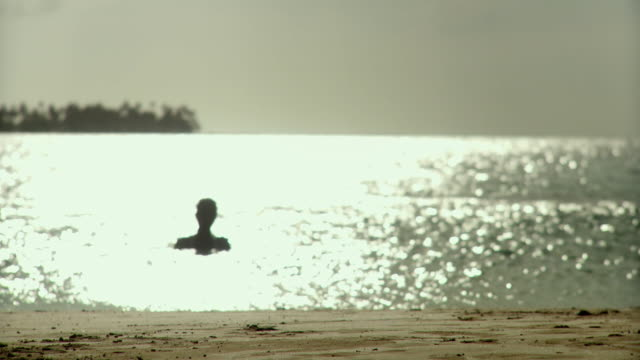 ws silhouette of young woman walking out of sea / scarborough, tobago, trinidad and tobago - trinidad trinidad and tobago stock videos & royalty-free footage