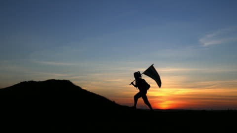 silhouette of   young woman walking with a flag - hill stock videos & royalty-free footage