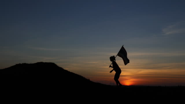 Silhouette of   young woman walking with a flag