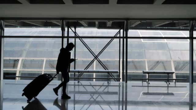 silhouette of young women with luggage walking at hong kong airport and holding smart phone device,travel concept, people in the airport.the traveler's suitcase - smart stock videos & royalty-free footage