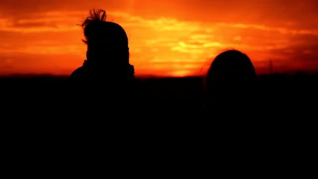 vídeos de stock e filmes b-roll de silhueta ao pôr do sol as pessoas estão feliz - vinheta