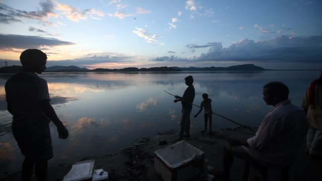 stockvideo's en b-roll-footage met silhouette people fishing in the brahmaputra river in the background of dramatic sunset sky, in guwahati on tuesday, 18 august 2020. - hobby's