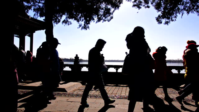 Silhouette: people on foot way in summer palace