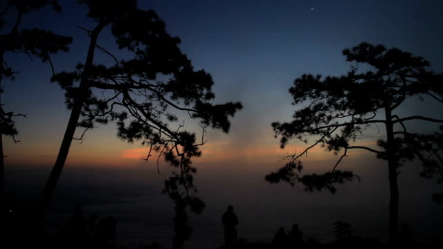silhouette people sunrise on the mountain.