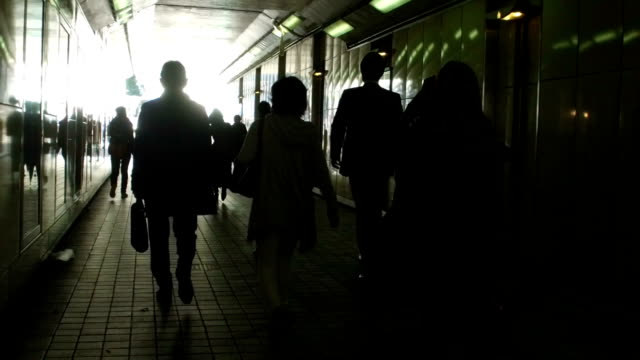 silhouette people walking in the tunnel - contrasts stock videos and b-roll footage