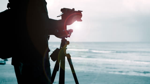 silhouette photographer setting function on camera - graphite stock videos & royalty-free footage