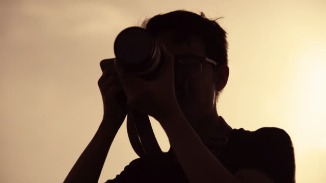 silhouette photographer using camera with telephoto lens to taking a picture. - twilight stock videos & royalty-free footage