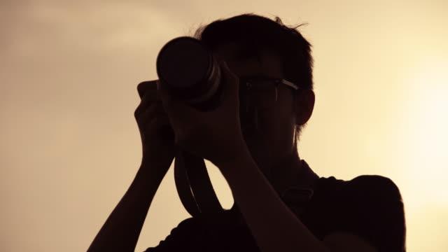望遠レンズ付きカメラを使って写真を撮るシルエットフォトグラファー。 - カメラ点の映像素材/bロール