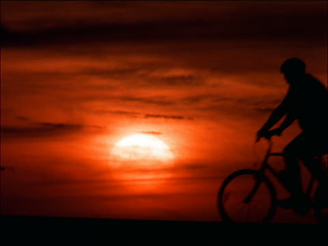silhouette profile man riding bicycle past camera at sunset / santa monica, california - lockdown viewpoint stock videos & royalty-free footage