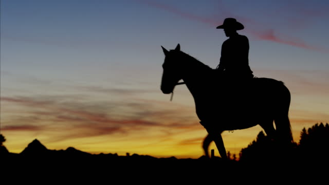Silhouette reveal Cowboy Rider in sunset wilderness Canada