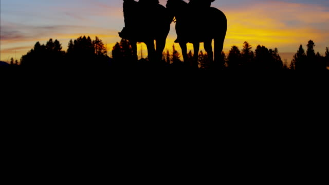 Silhouette reveal Cowboy Riders in sunset wilderness Canada