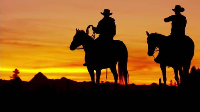vidéos et rushes de silhouette reveal cowboy riders in sunset wilderness canada - l'ouest américain
