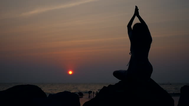 stockvideo's en b-roll-footage met de scène van het silhouet van meisje dat yoga op het strand bij zonsondergang praktizert - in kleermakerszit
