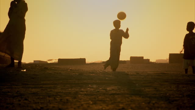 vídeos de stock e filmes b-roll de silhouette sequence of children playing football in the desert town of shalateen, egypt. - poverty