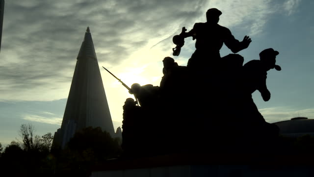 silhouette shot of a military statue in pyongyang with the ryugyong hotel in the background - pyongyang stock videos and b-roll footage