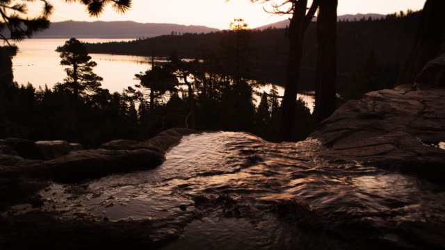 silhouette shot of a running stream shot at sunset near lake tahoe. - sunset bay state park stock videos & royalty-free footage