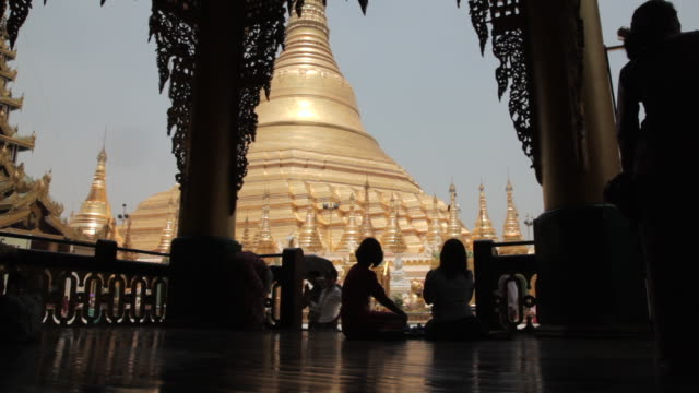 Silhouette shot of people sitting in the grounds of the Shwedagon Pagoda in Yangon.