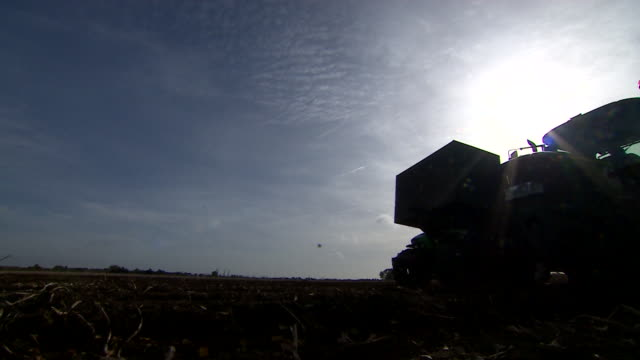 silhouette shot of tractors harvesting potatoes from a field - agricultural equipment stock videos and b-roll footage