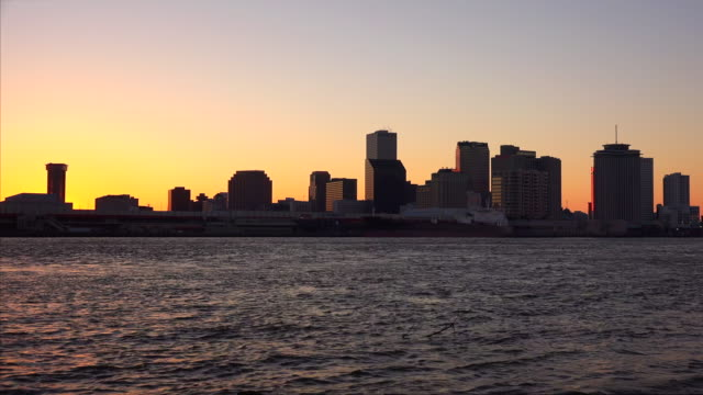 silhouette skyline of new orleans across the mississippi river at sunset - establishing shot stock videos & royalty-free footage