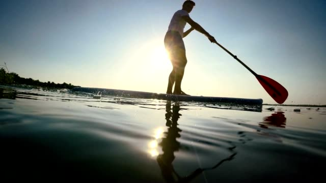 SLO-MO Silhouette stand-up-paddleboarding auf den See