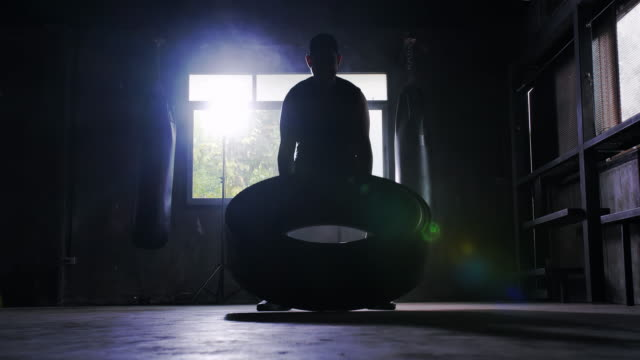 silhouette strong men are pushing the tires.men doing workout with big tire.athletic training hard at the gym.martial arts - in silhouette stock videos & royalty-free footage