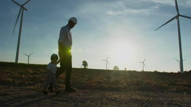 silhouette sonnenuntergang des asiatischen vaters ist ingenieur zu fuß in windkraftwerk mit kleinen baby junge alter 15 monate halten hand und blick auf die windkraftanlagen hintergrund mit großer freiheit zusammen. kinder über nachhaltigkeitskonzept un - single father stock-videos und b-roll-filmmaterial
