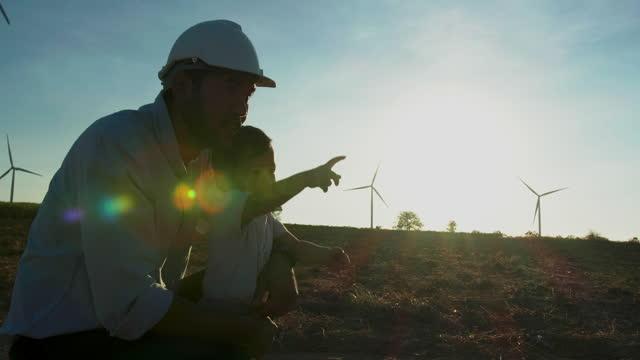 silhouette sonnenuntergang des asiatischen vaters ist ingenieur arbeitet in windkraftwerk mit kleinen baby junge im alter von 15 monaten blick auf die windkraftanlagen hintergrund mit großer freiheit zusammen. kinder über nachhaltigkeitskonzept unterrich - fuel and power generation stock-videos und b-roll-filmmaterial