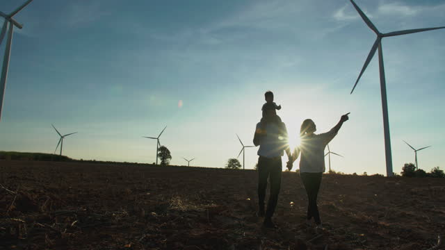 silhouette sunset of family,baby boy ride the neck of father and holding hand his wife while walk between the wind turbines with great freedom.helping hands concept. - environmental issues stock videos & royalty-free footage
