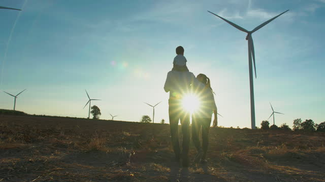 silhouette sunset of family,baby boy ride the neck of father and embrace his wife while walk between the wind turbines with great freedom.teaching children about sustainability concept. - futuristic stock videos & royalty-free footage