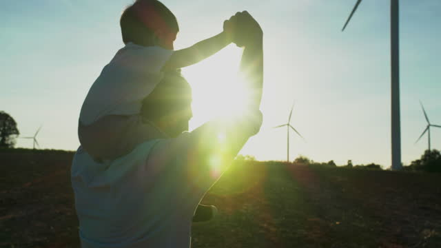 silhouette sunset of family,little baby boy age 15 month while ride the neck of father looking to the wind turbines background with great freedom.open arms concept.open arms concept. - wonderlust stock videos & royalty-free footage