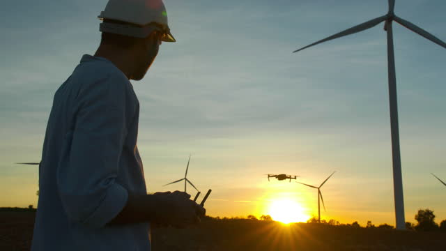 silhouette sunset of young male engineer controlling flying drone working at wind power station, inspect windmills farm for energy production.renewable energy plants concept. - hope stock videos & royalty-free footage